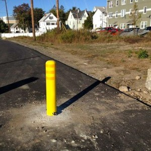 A yellow bollard stands out on the trail.