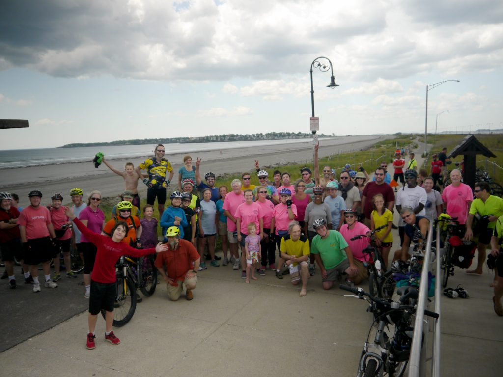 Bicycle riders pose for a photo near the beach.