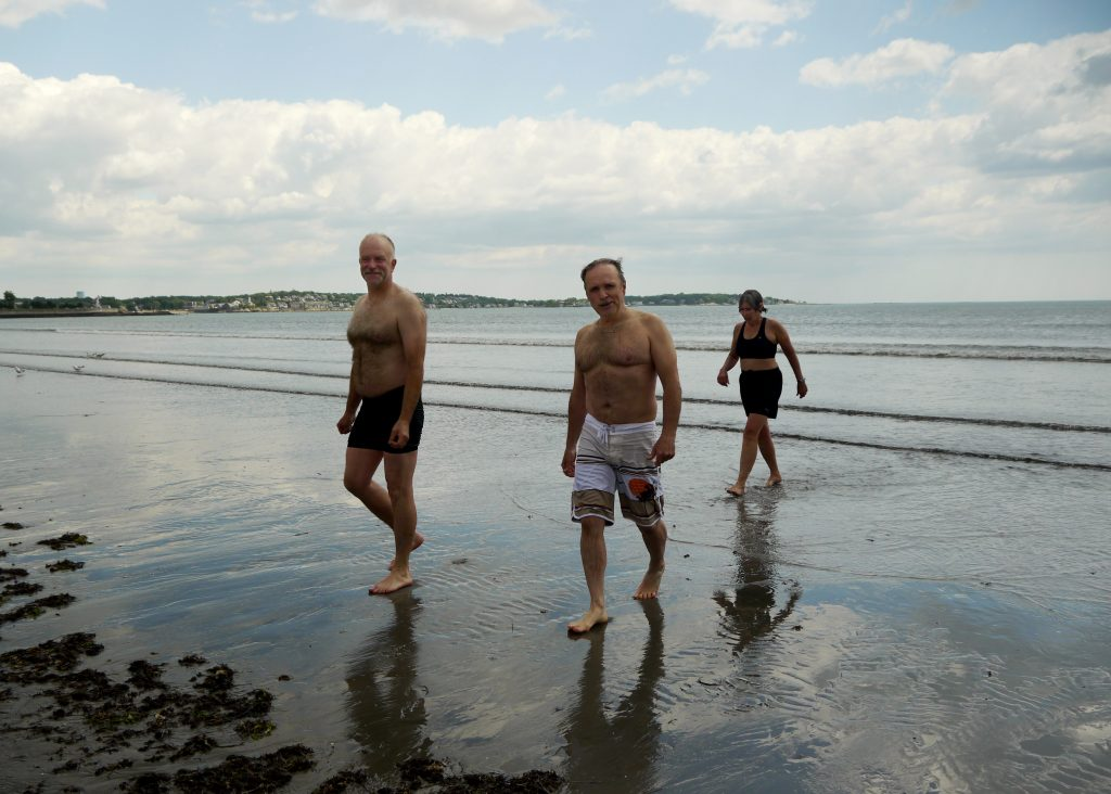 Three people walk out of the water at Nahant Beach.