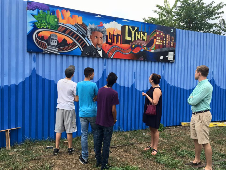 People look up at the mural along the trail in Lynn.