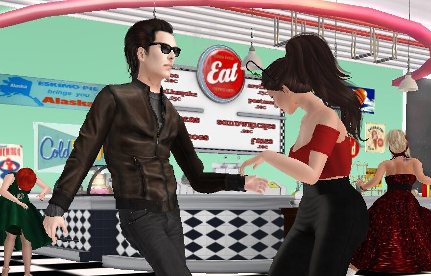 A guy and a woman dancing in a '50s diner.