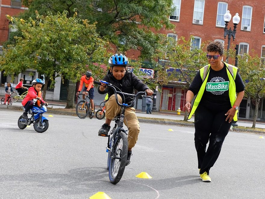 MassBike volunteer helping a child ride a bike.