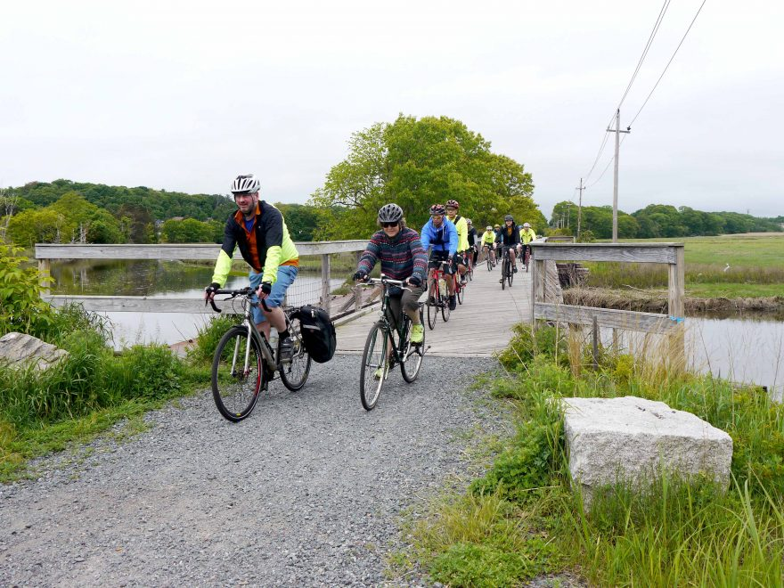 Cyclists ride over a bridge along the trail in Saugus.
