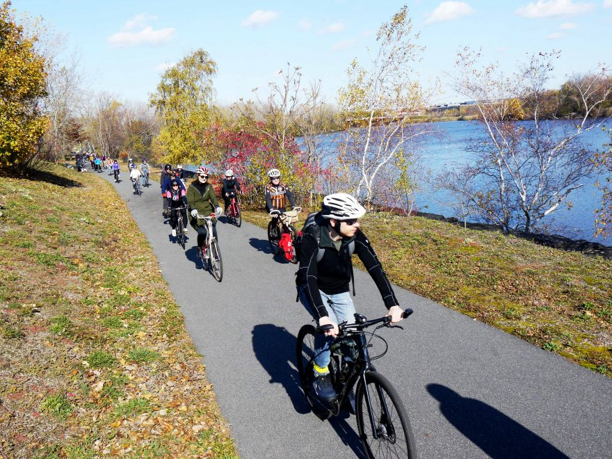 Bicyclists ride along the Malden River.