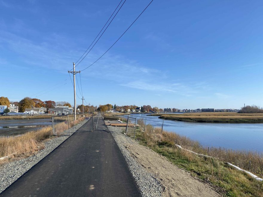 A newly paved road going through a salt marsh.